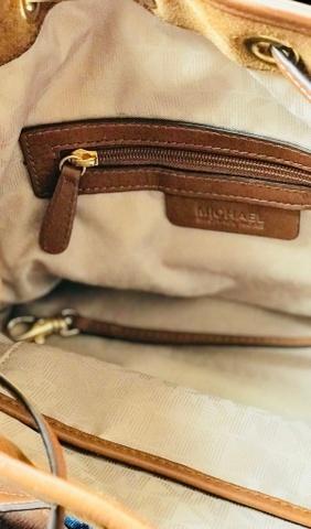Brun Michael Kors bucket veske i semsket skinn med gullfargede detaljer.